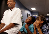 Denver Nugget's Center Marcus Camby, left, is interviewed by media as 4th graders Shontae Elie...