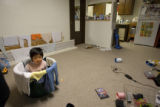 Alexander Song, 7, plays in a laundry basket in the front-room of his families home in Aurora...
