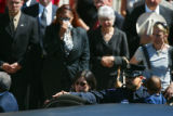 Mourners weep as Lt. Rich Montoya's son Eric Carrasco (bottom right) gets out of a limo on his way...
