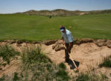 Superintendent  Dave Hensley (cq) works on a bunker on the 17th hole at the new Ballyneal Golf...