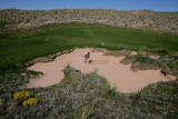 Brandon Arnold (cq) rakes out a bunker on the 8th hole at the new Ballyneal Golf Course, on...