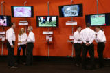 KAS099 Dish Network employees stand next to a display of new satellite receivers during the annual...