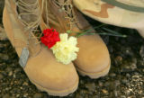 Flowers lay on a ceremonial pair of boots, helmet and dog tags at the future site of the Colorado...