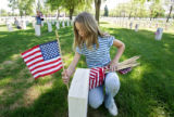 Traylor Elementary fifth grader Molly Rohde (cq), 11, places a flag on a grave at Fort Logan...