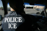 An Immigration and Customs Enforcement's Fugitive Operations team member waits for illegal...