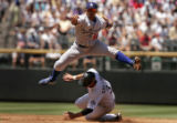Los Angles Dodger Rafael Furcal, top, leaps over Colorado Rockies player Cory Sullivan, bottom, as...