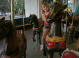 Brooke Bliss (cq), 4, of Thornton rides on the carousel Lakeside Amusment park Friday evening May...