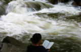 JPM085  Betsy Rotman (cq) reads as Boulder Creek swirls past her in Boulder, Colo., on Tuesday...