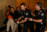 Marcus Richardson Sr. is restrained by deputies after becoming aggressive towards the media as he...