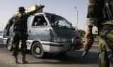 (NYT10) BAGHDAD, Iraq -- June 14, 2006 -- IRAQ-6 -- A van carrying an empty coffin is directed to...
