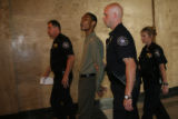 Marcus Richardson acknowledges a friend in the hallway as is escorted out of the courtroom by...
