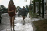 Sisters Vanessa Addleman, 10 at left, and Kristen, 15, play in the rain run-off of one-hour of...