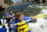 New Life program member Mike Kripakov (cq, center), 36, paddles with raftmates through some small...