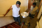 KAS021 Joseph Agune (cq), left, and Desalegin Yehune (cq) carry food out of a kitchen in the...