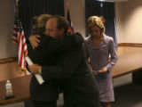 ( LT. to RT.) Jennifer Garrett-Buck (CQ), of Oklahoma, is hugged by Colorado Attorney General John...