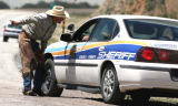 Rancher Brett Shawcroft (cq) talks to a Costilla County Sheriff Deputy on Hwy. 160 about ten...