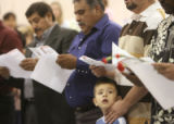 Four year-old Raul Acosta Jr. of Denver stands with his father, Raul Acosta (cq) during a United...