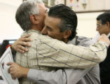 Osvaldo De La Casa, left, of Argentina hugs his son Daniel who is clutching his naturalization...