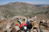 Chad Goare (cq), left, Ty Pixler (cq), center, and their dog Clifford, right, rest at the summit...