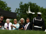 A lone dove flies over the family of Ensign Robert Keller druing a funeral service at Fort Logan...