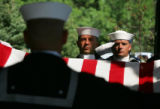 A Naval honor folds the colors during a funeral for Ensign Robert Keller at Fort Logan National...