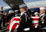 A Naval honor guard carries the casket of Ensign Robert Keller, who was killed in WWII, on the...