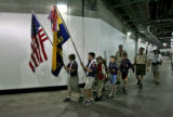 Ryan Layton, carrying the American flag, leads Cub Scout Pack #467, of Centennial, CO, to the...