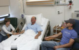 Judy Harlon sits adjacent to her husband Terry Harlon in his recovery hospital bed during the...