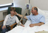 Judy Harlon sits adjacent getting a comforting stroke from her husband Terry Harlon in his...