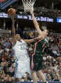 Denver Nuggets center Marcus Camby, left, puts up a shot over  Milwaukee Buck center Andrew Bogut,...