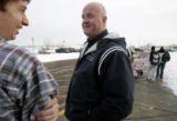Ed Clark, right,  visits with student Jason Lightfoot, who is waiting for a ride at the end of the...