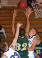 Aurora Central's Caston Mabin,middle (32), has his shot blocked by  Grandview's Matt Parker,...