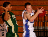 Aurora Central's Caston Mabin, left, guards Grandview's Tyler Gross, right, as Gross pulls down a...