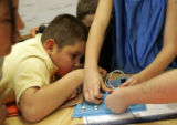 Jose Ravera (cq), 8, tries to peak through the hands of his group  in Emily Taylor's third grade...