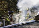 N0103FIRE.JPG Smoke pours from a hole firefighters from Sugarloaf fire department cut in the roof...
