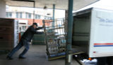 Marv Lich (cq) pushes a bin filled with packages into one of the USPS buses at the dock of the...