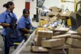 DM0769   Tamara Paris, left, and Regina Jones load boxes onto a conveyor that feeds an automated...