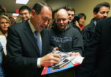 Republican presidential candidate Mike Huckabee signs an autograph while campaigning at Des Moines...