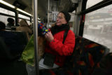 Margaret Stearns, 47, all layered for the cold makes her way by bus to her next destination,...