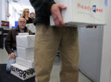 Eric Bartczak (cq) carries a pile of packages as he in line at the Cherry Creek USPS office on...