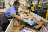 DM0581   Regina Jones loads packages onto an automated sorter at the Denver Bulk Mail Center in...