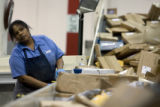 DM0735   Regina Jones loads packages onto an automated sorter at the Denver Bulk Mail Center in...