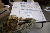DM0416   Staff Sgt. Carlyof Fort Collins fills out her bag tags as she andmore than 200 members of...