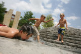 (from left) 5 year-old Brandon Farmelo (cq) lays on the concrete next to one of the fountains at...