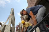 Unidentified construction workers (did not wish to disclose their names) work on a group of...