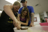 Oneica Trasvina(cq), 10, and her friend Deonna Kysar(cq), 13, stir brownie batter as her father,...