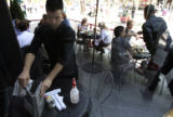 Carmine Diaz, (cq) resets a table on the patio for turnover to new customers at The Rialto Cafe at...