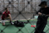Ben Petrick spends time in the batting cage with Glencoe High School sophomore Jason Miller, 15,...