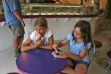 Meggi Wisk (cq), left, and friend Rebecca Sandell (cq), both 11 years old, eat some ice-cream, at...