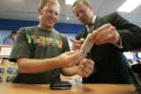 383 Gregg Davis, CQ, 36, left, of Denver, gets a personal demonstration of the new iPhone by...